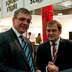 Brandenburgs Bauminister Jörg Vogelsänger (rechts) besucht Ofenexperte.de auf der Eigenheimmesse in Erkner.